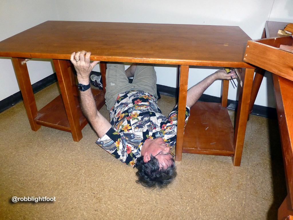 Photo of Robb under his desk - not having fun